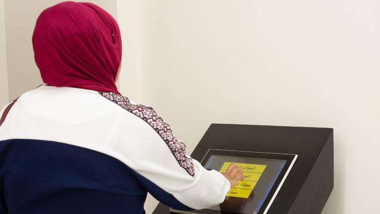 سيدة أردنية أمام ماكينة الصراف الآلي لبرنامج التحويلات النقدية