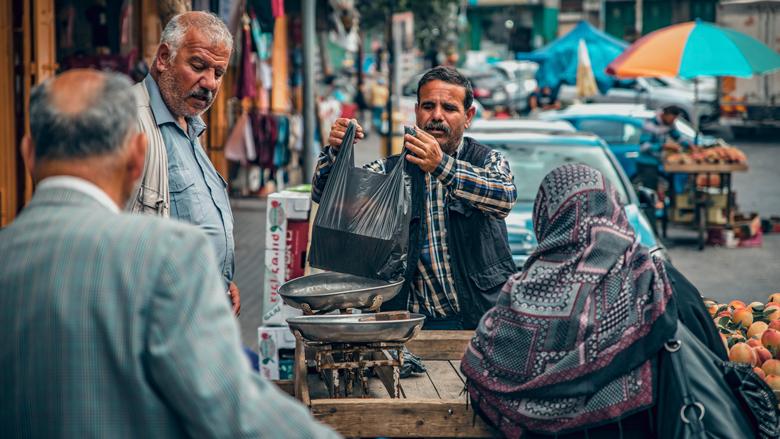 فلسطينيون يشترون الفاكهة في أحد الأسواق.